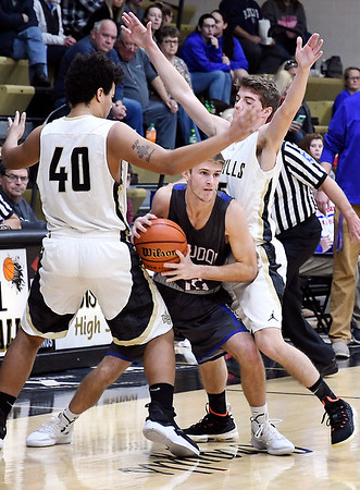 John P. Cleary | The Herald Bulletin<br /> Elwood's Ben DeLong gets trapped near mid-court by Madison-Grant's Isaac Cooper and Kaden Howell.