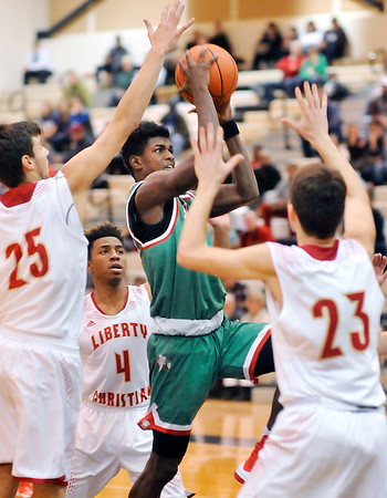 John P. Cleary |  The Herald Bulletin<br /> Anderson's Zakarius Milhouse drives through three Liberty Christian defenders as he takes the ball to the basket.