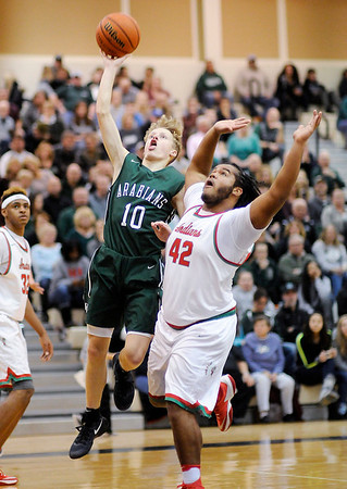 Don Knight | The Herald Bulletin<br /> Pendleton Heights' Karsten Windlan shoots a layup as he is guarded by Anderson's Keaton Davis during the Boys Madison County Basketball Tournament on Saturday. Windlan scored 24 points.