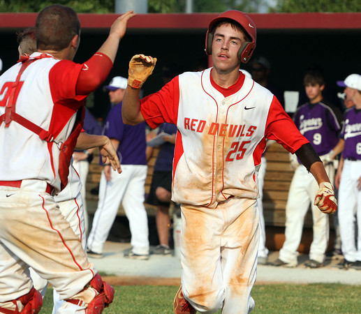 Jeffersonville junior Nick Gallahger is welcomed home after hitting a triple and scoring in the Red Devils' 6-4 win over Seymour for the 4A Sectional crown. Staff photo by C.E. Branham