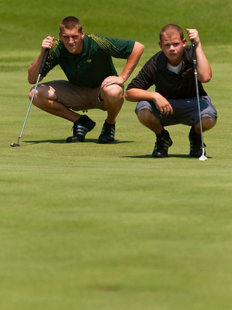 Floyd Central High School junior Daniel Shepard, left, and New Albany High School senior Tyler Banet study the contours of the third green before putting during the Hoosier Hills Conference golf meet at Covered Bridge Golf Club on Saturday afternoon. Staff photo by Christopher Fryer
