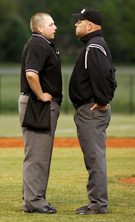 The umpires discuss a controversial call at first base during the fifth inning of the high school baseball game between Floyd Central High School and Providence HIgh School at Floyd Central on Friday night. Floyd Central won the game 9 to 3. Staff photo by Christopher Fryer