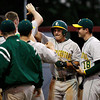 Floyd Central High School outfielder Kyle Neafus is congratulated by his teammates after scoring during the fifth inning of their game against Jeffersonville High School at Jeffersonville on Wednesday night. Floyd Central won the game 8-5. Staff photo by Christopher Fryer