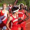 Jeffersonville junior Tyrell Dowdell hands the baton to senior Thomas Kimbrell in the 4x800 relay race of the 2012 IHSAA track and field sectional at Jeffersonville. Staff photo by C.E. Branham