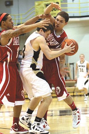 Jeffersonville defenders Trice Whaley, left, and Myles Harvey cage in Corydon Central guard Joseph Hinton Tuesday night at Corydon Central.  Staff photo by C.E. Branham