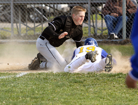 Henryville catcher Jordan Hahn tags out New Washington player Austin Roberts at the plate Monday afternoon at New Washington. Staff photo by C.E. Branham