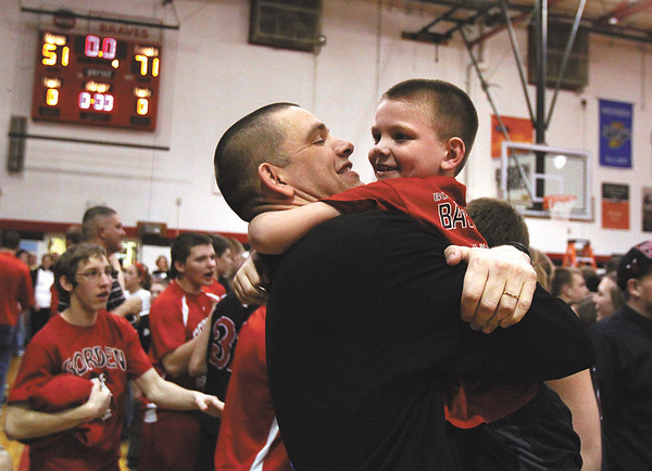 Borden coach Doc Nash hugs his son Kaysm after the Braves beat South Central 71-51 Monday night for the 1A sectional crown.  Staff photo by C.E. Branham
