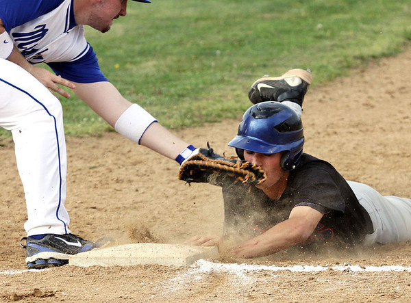 Silver Creek base runner Shawn Pezullo dives safely back to first ahead of the tag by New Washington first baseman Brad Baker. Silver Creek visited New Washington on Tuesday. Staff photo by C.E. Branham