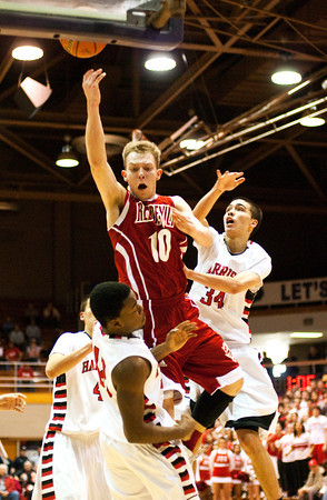 Jeffersonville junior Drew Ellis is fouled while going up for a shot during their game against Evansville Harrison in the regional tournament at Seymour on Saturday. Jeffersonville won the game, 73-62. The Red Devils went on to defeat Franklin Central 85-69 for the regional title on Saturday night. Staff photo by Christopher Fryer