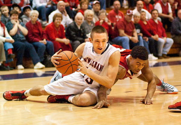 New Albany senior William Arnold and Jeffersonville senior Darryl Baker scramble for a loose ball during the championship game of the Seymour Sectional on Saturday. Jeffersonville won the game,  63-50. Staff photo by Christopher Fryer