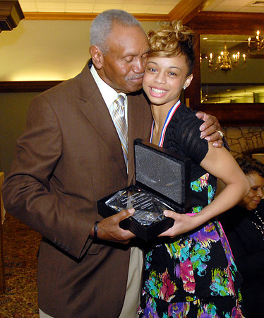 Johnny Wilson gives Darien Thompson, of Anderson High School, a hug as he presents her with the 2013 Johnny Wilson Award for all-around athletic excellence.