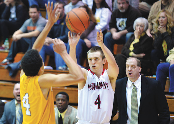 New Albany junior Evan Milligan pulls up for a 3-point shot over the defense during the Bulldogs' 47-45 win over Evansville Central in the first round of the Class 4A Regionals held at Seymour Saturday.<br /> Staff photo by Tyler Stewart