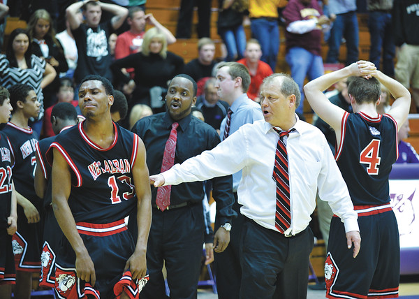 New Albany head coach Jim Shannon consoles senior guard Leondre McBirth after the Bulldogs' 46-45 loss to Bloomington North in the Class 4A Regional Championship at Seymour Saturday evening.<br /> Staff photo by Tyler Stewart