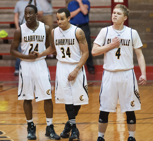 Clarksville seniors Marquise Parrish (left), Andrew Jones (center) and Calvin McEwen look on as fellow senior D.J. Coleman shoots a pair of free throws in overtime of Saturday's Class 2A Southridge Regional Championship game. Photo by Joe Ullrich