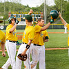 Kyle Neafus, right, and Ross Lundy are congratulated by their teammates after scoring on a three-run RBI double by Kyle Beach during the third inning of their game against Seymour at Floyd Central on Wednesday. Floyd Central won the game, 8-1. Staff photo by Christopher Fryer