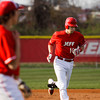 Jeffersonville's Drew Ellis approaches home plate after hitting a home run during the Red Devils' home game against Floyd Central on Wednesday. Staff photo by Christopher Fryer
