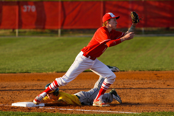 Floyd Central's Dalton Drexler is forced out at third base by Jeffersonville's Josh Burke during their game at Jeffersonville on Wednesday. Staff photo by Christopher Fryer