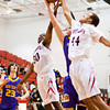 New Albany forward DeAnthony Warren, left, and center Nick White go up for a rebound during the Bulldogs' home game against Scottsburg on Saturday. New Albany won the game, 77-59. Staff photo by Christopher Fryer