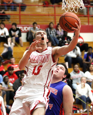 Jeffersonville junior Drew Ellis slodes by the Jennings County defense for a reverse layup Thursday night. Staff photo by C.E. Branham