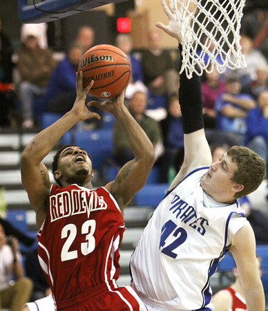 Jeffersonville senior Darryl Baker scores against Charlestown defender Tristan Chester Tuesday night. Staff photo by C.E. Branham