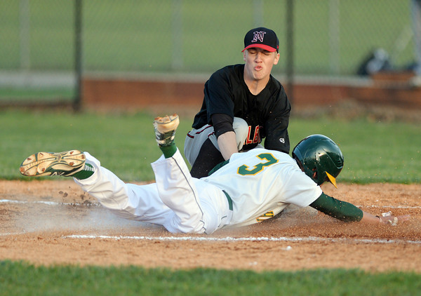 New Albany pitcher Noah Smith tags out the runner at home plate during Floyd Centrals' 12-4 victory over the Bulldogs Wednesday evening.<br /> Staff photo by Tyler Stewart