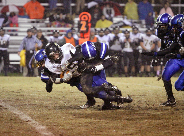 Corydon Central running back Shane Brown is hit for a loss by Charlestown defenders Friday night in Sectional play. Staff photo by C.E. Branham