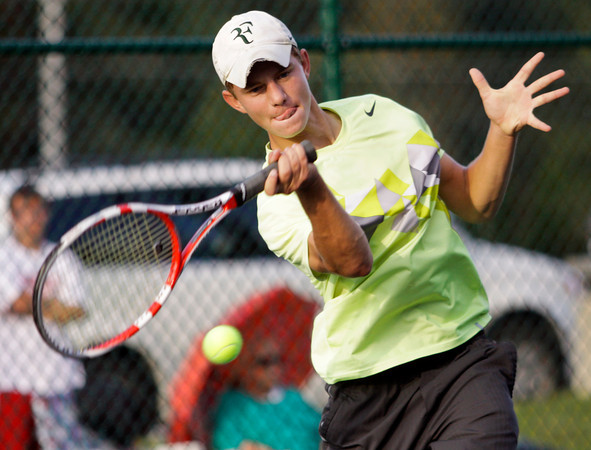Floyd Central senior Ryan Plunkett moves to return a shot to Jeffersonville junior Austin Hunt during their No. 1 singles match in the final round of the Floyd Central Regional on Wednesday. Hunt won the match in 3 sets, 6-0, 2-6, 6-2. Staff photo by Christopher Fryer