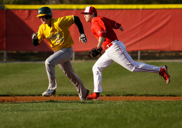 Floyd Central's Kyle Beach is tagged out by Jeffersonville's Jared Burke during a rundown in their game at Jeffersonville on Wednesday. Staff photo by Christopher Fryer