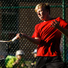New Albany freshman Logan Charvonneau returns a shot to Floyd Central senior Ryan Plunkett during their No. 1 singles match in the regional tournament at Floyd Central on Tuesday. Staff photo by Christopher Fryer