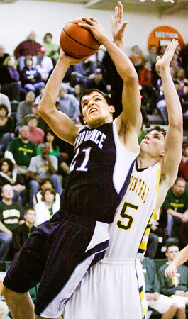 Providence center Ryan Pickerrell rises above Floyd Central center Codie Hamsley during their game at Floyd Central on Saturday. Providence won the game, 43-31. Staff photo by Christopher Fryer