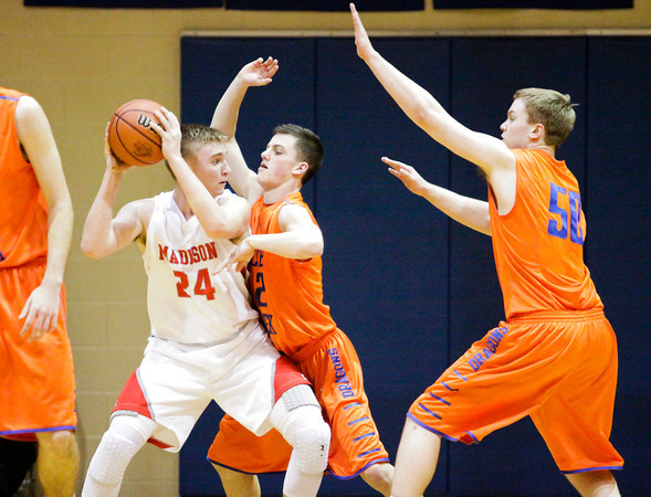 Silver Creek guard Brooks Howell and center Christian Reed, right, put pressure on Madison forward Carson Wattenbarger during their game at the North Harrison Sectional on Wednesday. Staff photo by Christopher Fryer