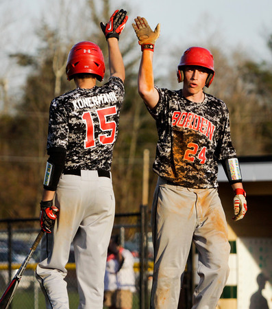 Borden's Garrett Vick is congratulated by Travis Konermann after scoring during the Braves' 8-7 victory over Floyd Central on Thursday. Staff photo by Christopher Fryer