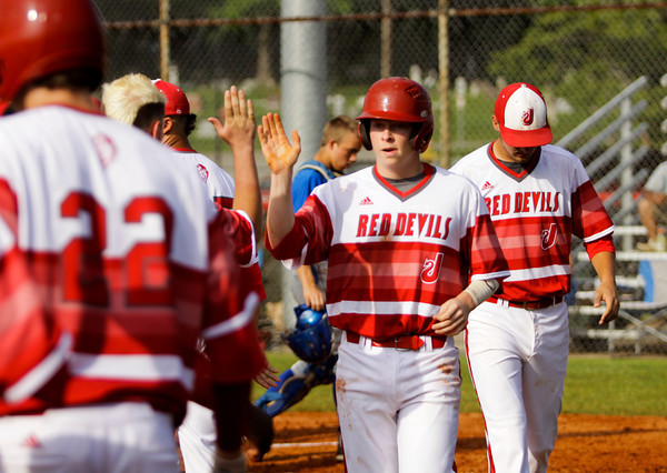 Jeffersonville sophomore Ian Ellis is congratulated by his teammates after scoring during the Red Devils' 4-0 win over Jennings County at the New Albany Sectional on Wednesday. Staff photo by Christopher Fryer