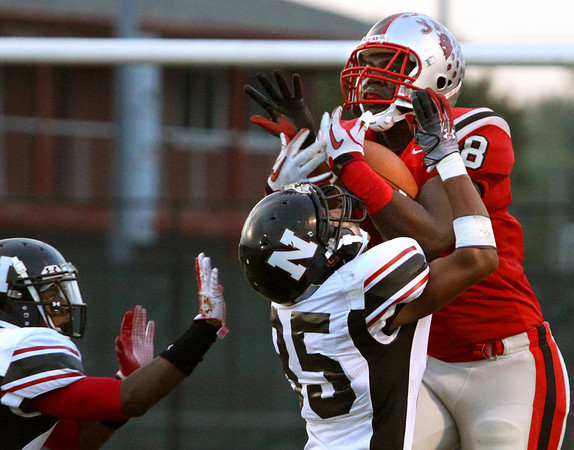 Jeffersonville tight end Dionte Allen pulls in a 39-yard reception over the coverage of New albany defenders Devin Higgins (35) and Jeffontae McClain Friday night at Blair Field. Staff photo by C.E. Branham