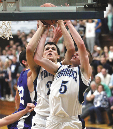 Providence players Nano Grantz and Ryan Pickerrell battle for a rebound Friday night against New Washington. Staff photo by C.E. Branham