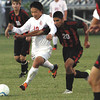 Jeffersonville senior forward Brian Fischer tangles with New Albany defender Bryan Kong in a match Tuesday night at Jeffersonville. Staff photo by C.E. Branham
