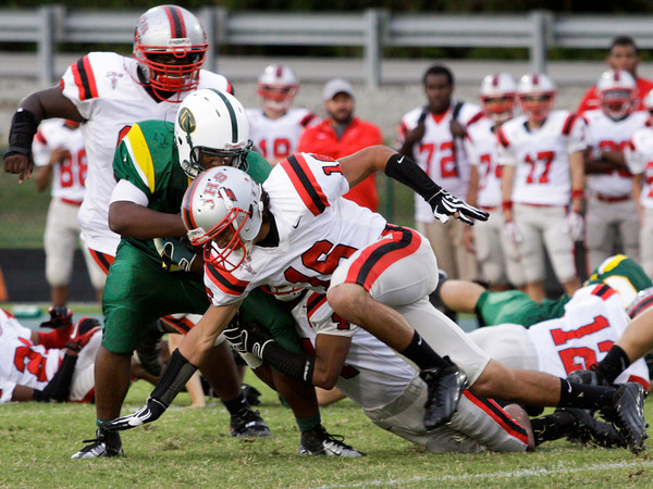Jeffersonville defensive backs David Morales and Damin Smith stop Floyd Central running back Garry Posey during the first quarter of their game at Floyd Central on Friday. Staff photo by Christopher Fryer