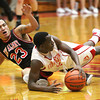 Jeffersonville senior Jacquari Chandler wins a loose ball with with New Albany player Jermaine Parrish. Staff photo by C.E. Branham