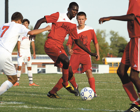 Rock Creek player Gedeon Nzambi passes to a teammate in a match with Silver Creek on Thursday. Staff photo by C.E. Branham