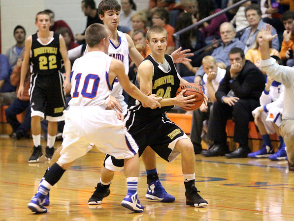 Henryville guard Landon Guthrie looks for help after being trapped by Silver creek players Shae Durham (10) and Jake Steele. Staff photo by C.E. Branham