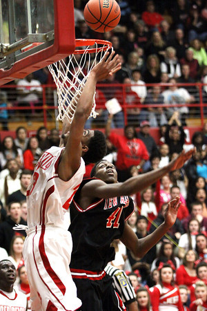 Jeffersonville senior Darryl Baker tips in two of his 26 points over New Albany center Anthony Edwards. Staff photo by C.E. Branham