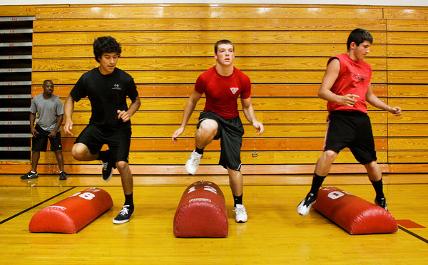 Jeffersonville High School assistant coach Keith Phillips Sr. looks on as he works with, from left, David Morales, Dalton Adkins and Dylan Montgomery during pre-season football conditioning in the gymnasium on Tuesday evening. Staff photo by Christopher Fryer