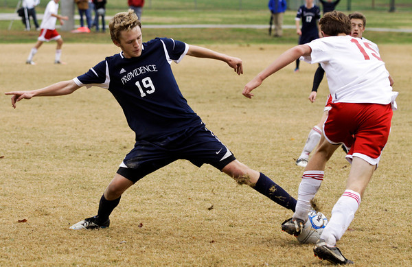 Providence midfielder John Murray attempts to steal the ball from Evansville Mater Dei midfielder Adam Kissel during the second semifinal of the Class A Floyd Central Semistate on Saturday. Providence won the game in overtime, 3-2. Staff photo by Christopher Fryer