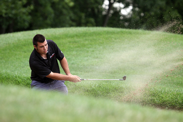 New Albany golfer Corey Embry hits out of a trap on the eighth hole of the IHSAA Golf Sectional on Monday at Covered Bridge Golf Club. Staff photo by C.E. Branham