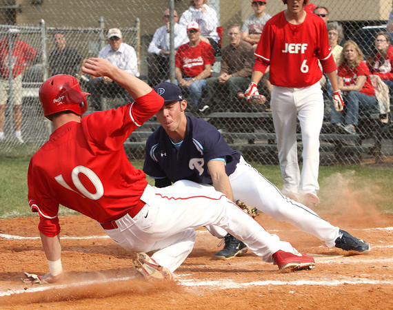 Providence pitcher Jon Davis tags out Jeffersonville runner Drew Ellis at the plate after a wild pitch. Staff photo by C.E. Branham