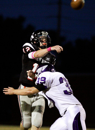 New Albany senior Michael Diehl gets a pass off before being hit by Seymour senior Seth Gorman during the first half of their game at New Albany on Friday. New Albany lost the game, 22-20. Staff photo by Christopher Fryer