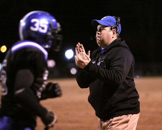 Charlestown coach Jason Hawkins gives him Pirates a hand as they come off the field in the first half. Staff photo by C.E. Branham