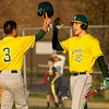 Floyd Central's Charlie Loveall is congratulated by Colton Kimm after scoring in the fifth inning of the Highlanders' game at Jeffersonville on Wednesday. Staff photo by Christopher Fryer