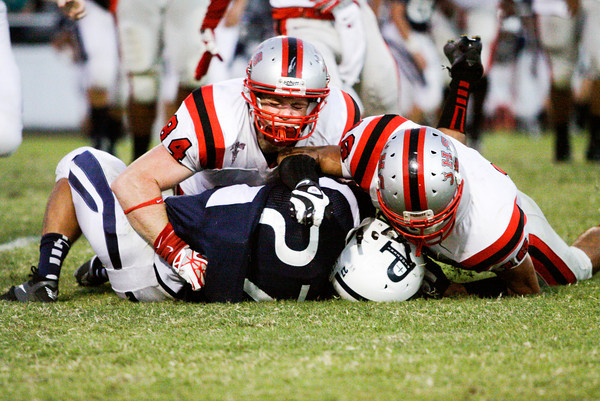 Jeffersonville's Dalton Adkins, left, and David Morales take down Providence running back Matt Bell during their game at Providence on Friday. Staff photo by Christopher Fryer