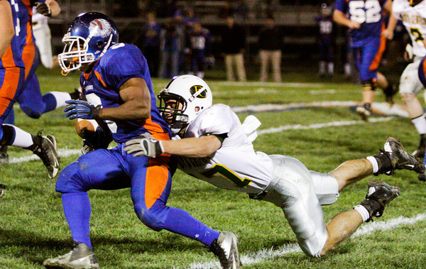 Defensive back Brandon Stout dives to tackle running back Jefferey Wooten during Floyd Central's sectional championship game at Whiteland on Friday. The Highlanders lost the game, 41-20. Staff photo by Christopher Fryer